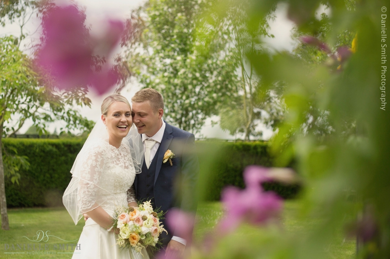 bride and groom laughing through pink flowers - maidens barn wedding