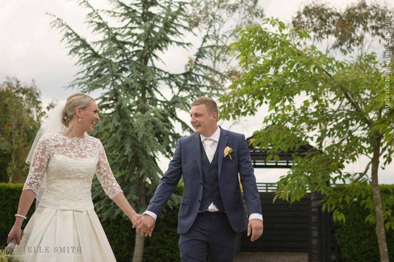 bride and groom walking through garden - maidens barn wedding