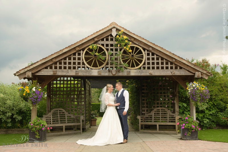 bride and groom standing by wooden structure - maidens barn wedding