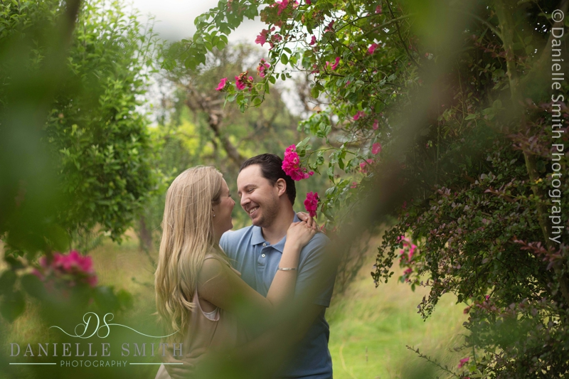 couple smiling at each other - pre-wedding garden photo shoot