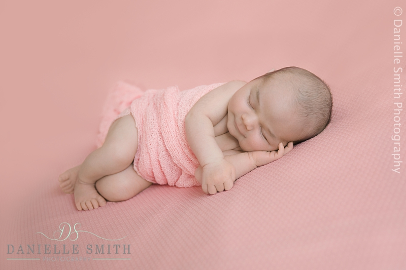 newborn baby girl on pink background