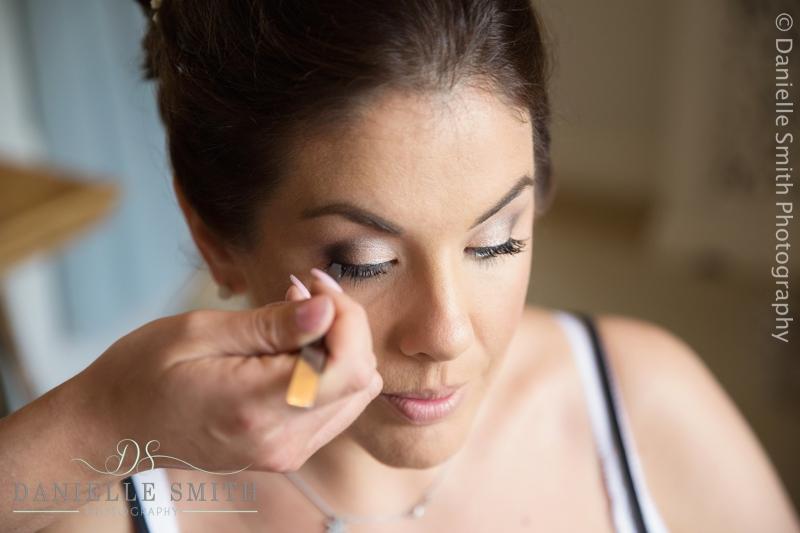 bride having her make up done at houchins