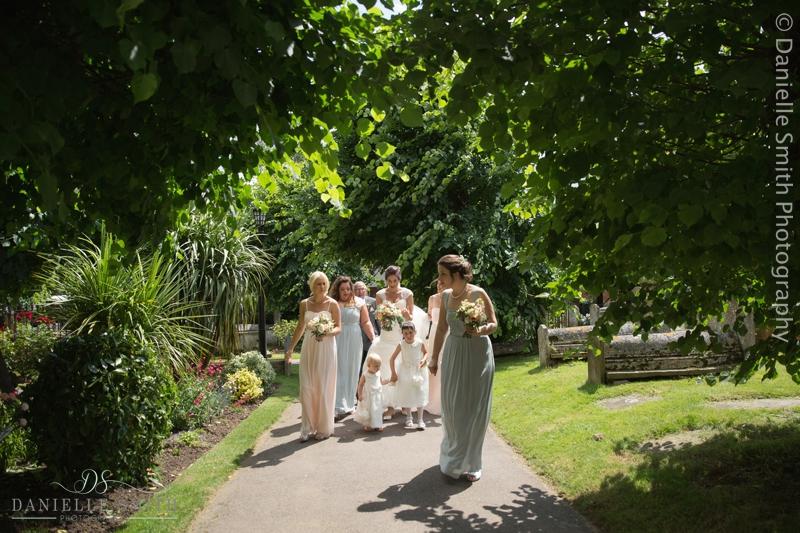 bride and bridesmaid walking towards church - creative documentary wedding photography