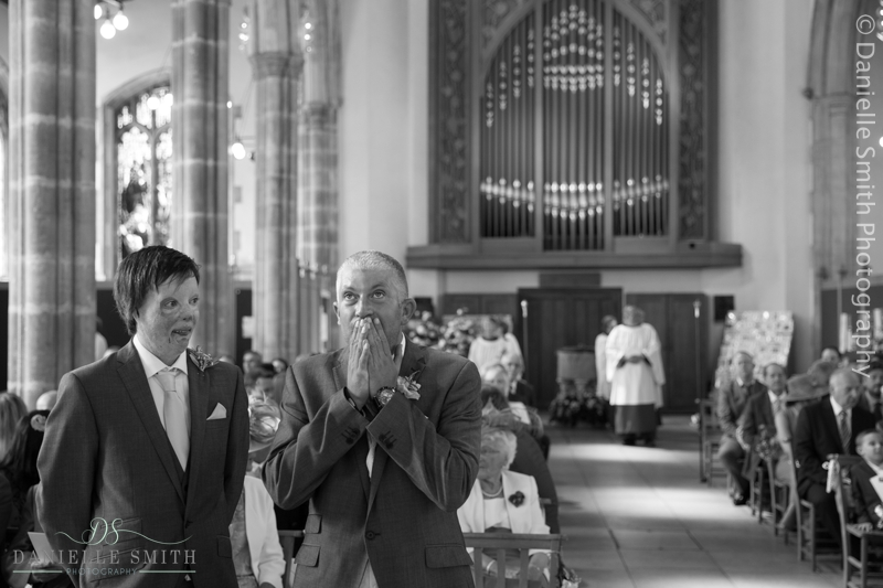 groom with hands on mouth waiting for bride