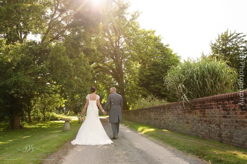bride and groom walking down drive at houchins wedding