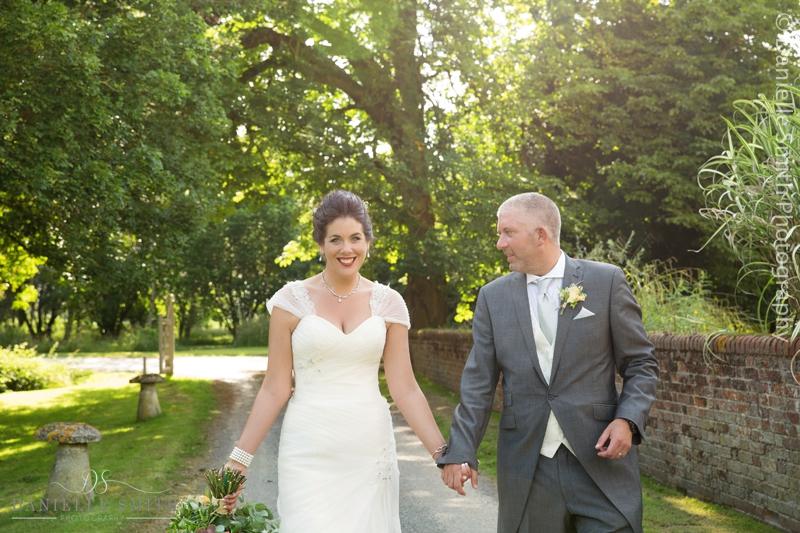 groom looking at his bride as they walk