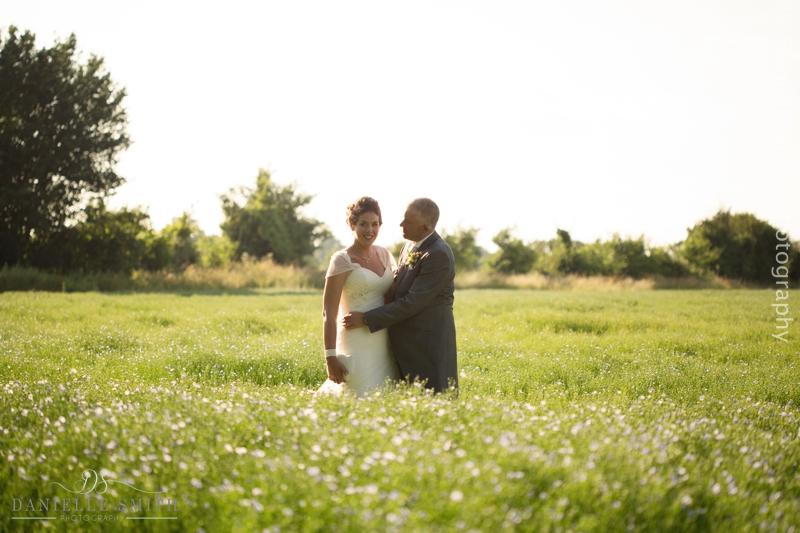 bride and groom in flower field at houchins wedding