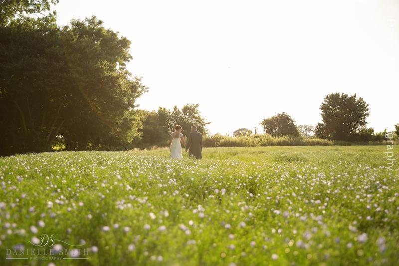 bride and groom walking through flower field at houchins