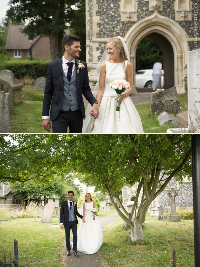bride and groom walking through church gardens