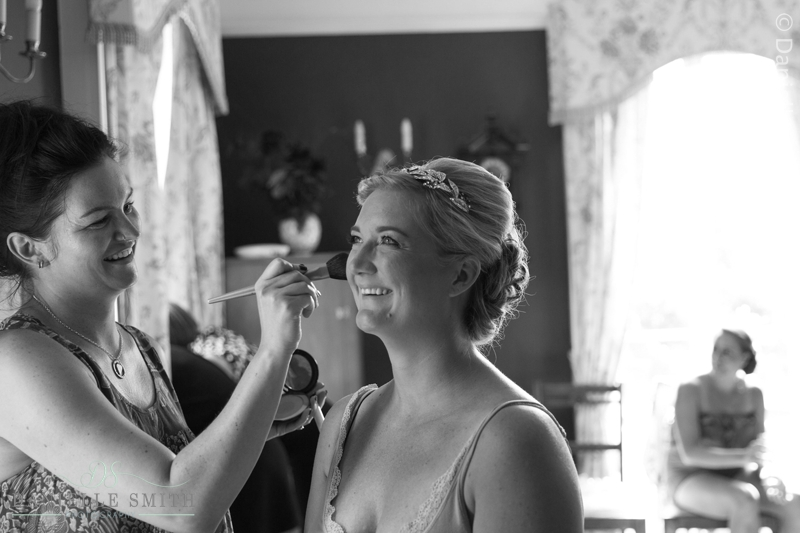 bride smiling while having make up done at mulberry house