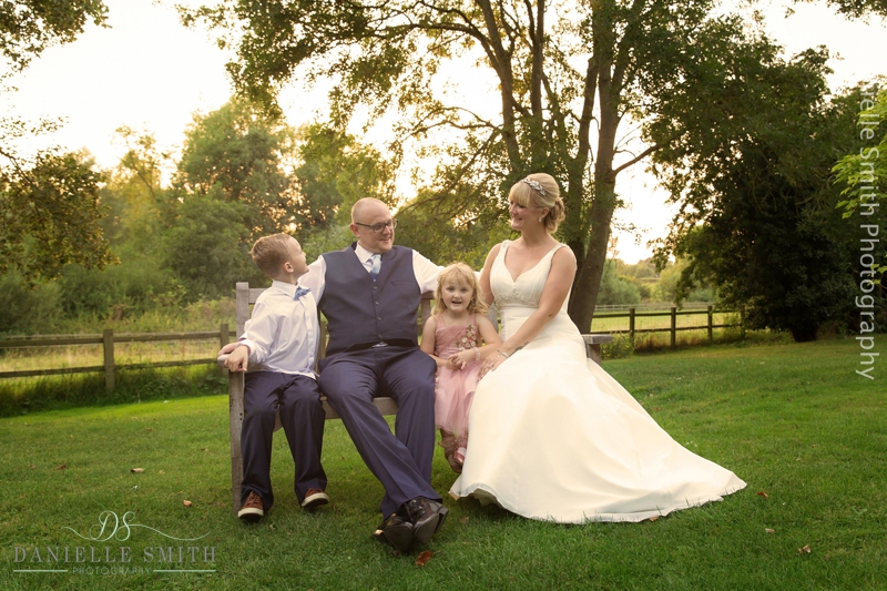 bride and groom and kids sitting on bench