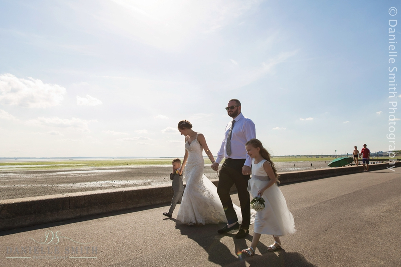 bride and groom and children at beach