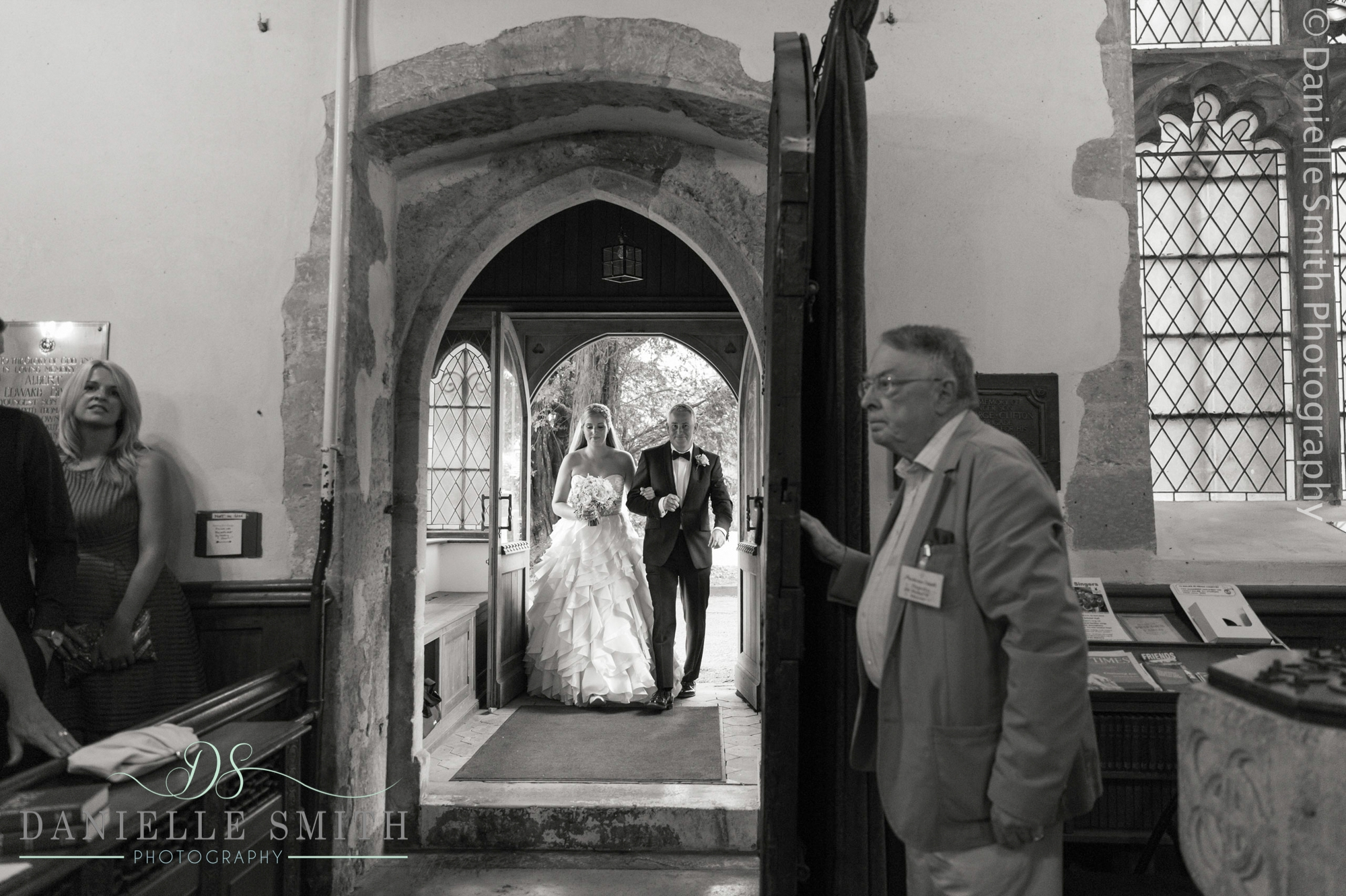 bride and father walking into church
