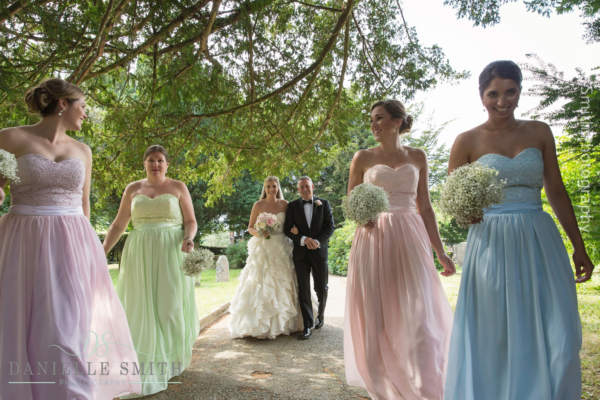 bride and her dad and bridesmaids walking to church