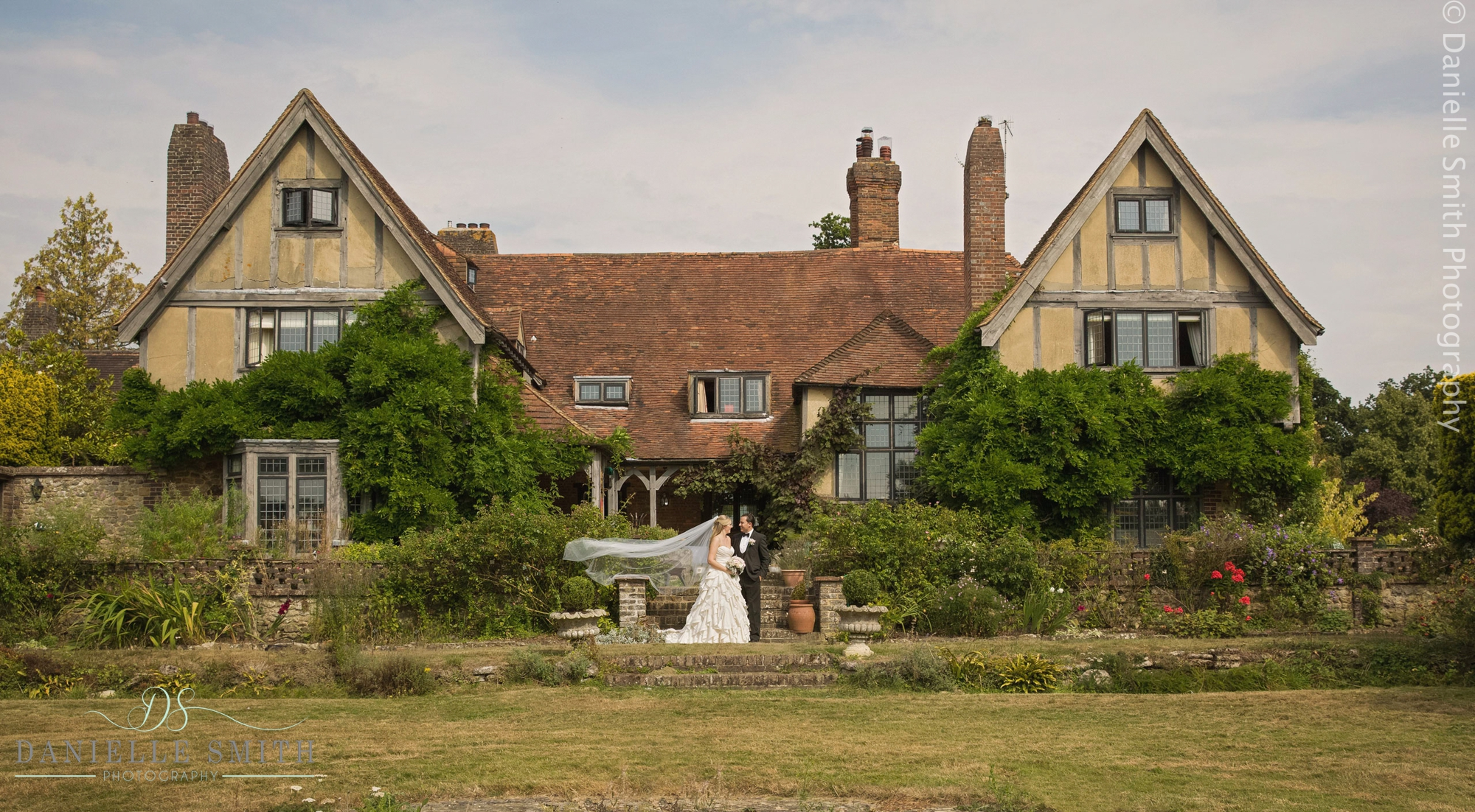 bride and groom outside house in kent - summer garden wedding