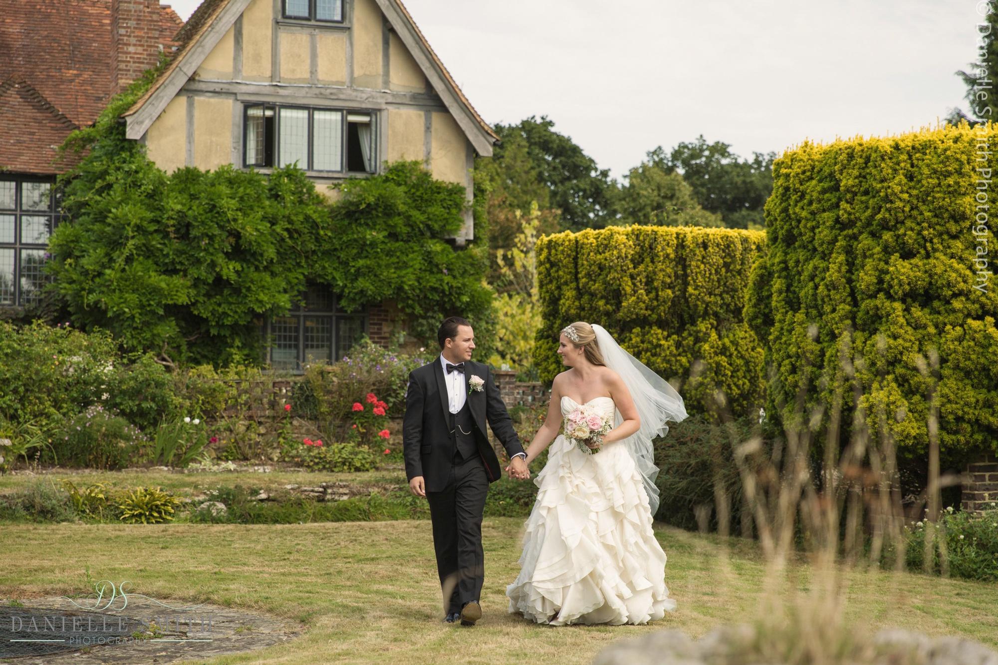 bride and groom walking through gardens - summer garden wedding