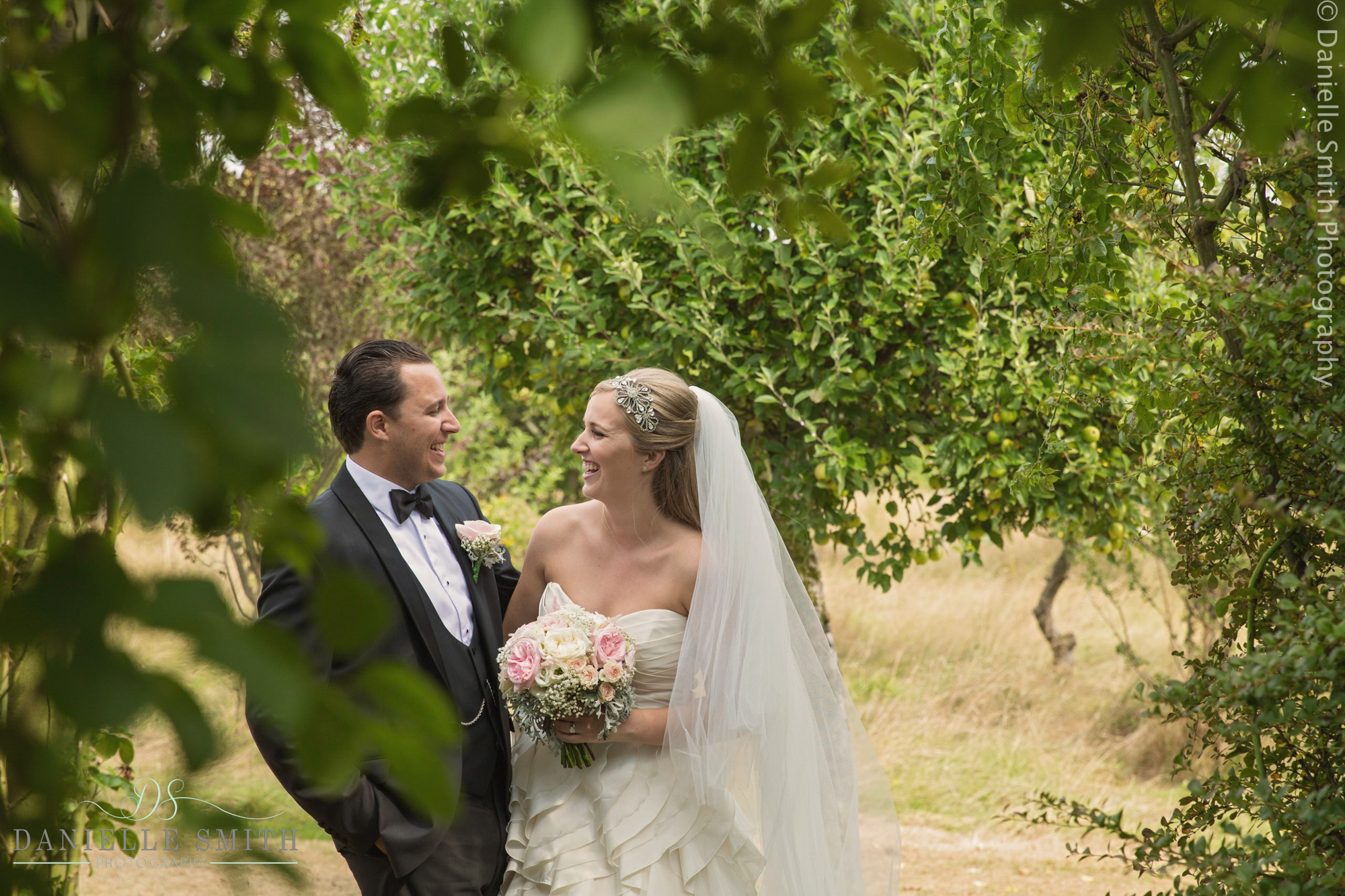 bride and groom laughing in gardens in kent