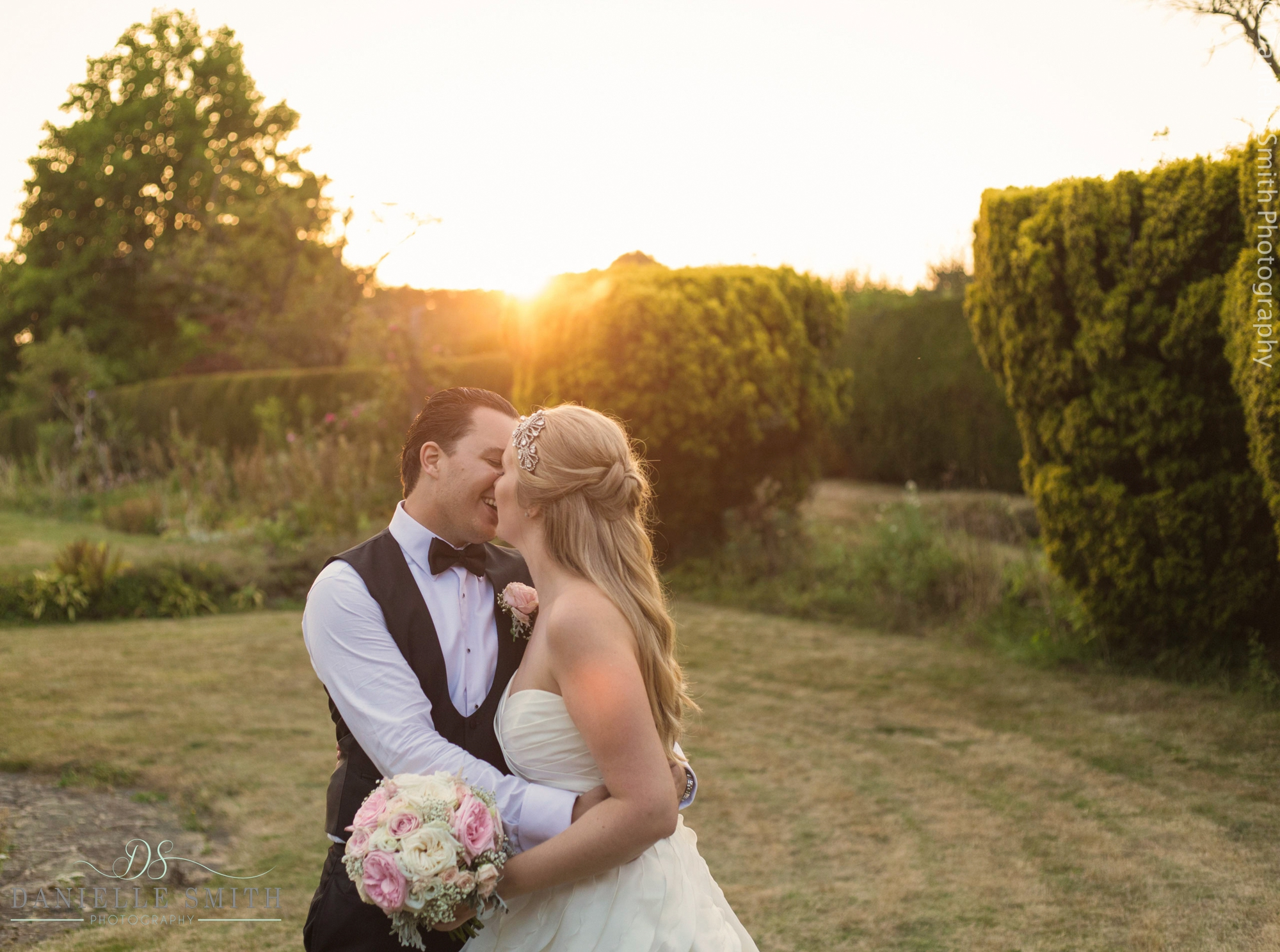 bride and groom kissing as sun goes down - summer garden wedding