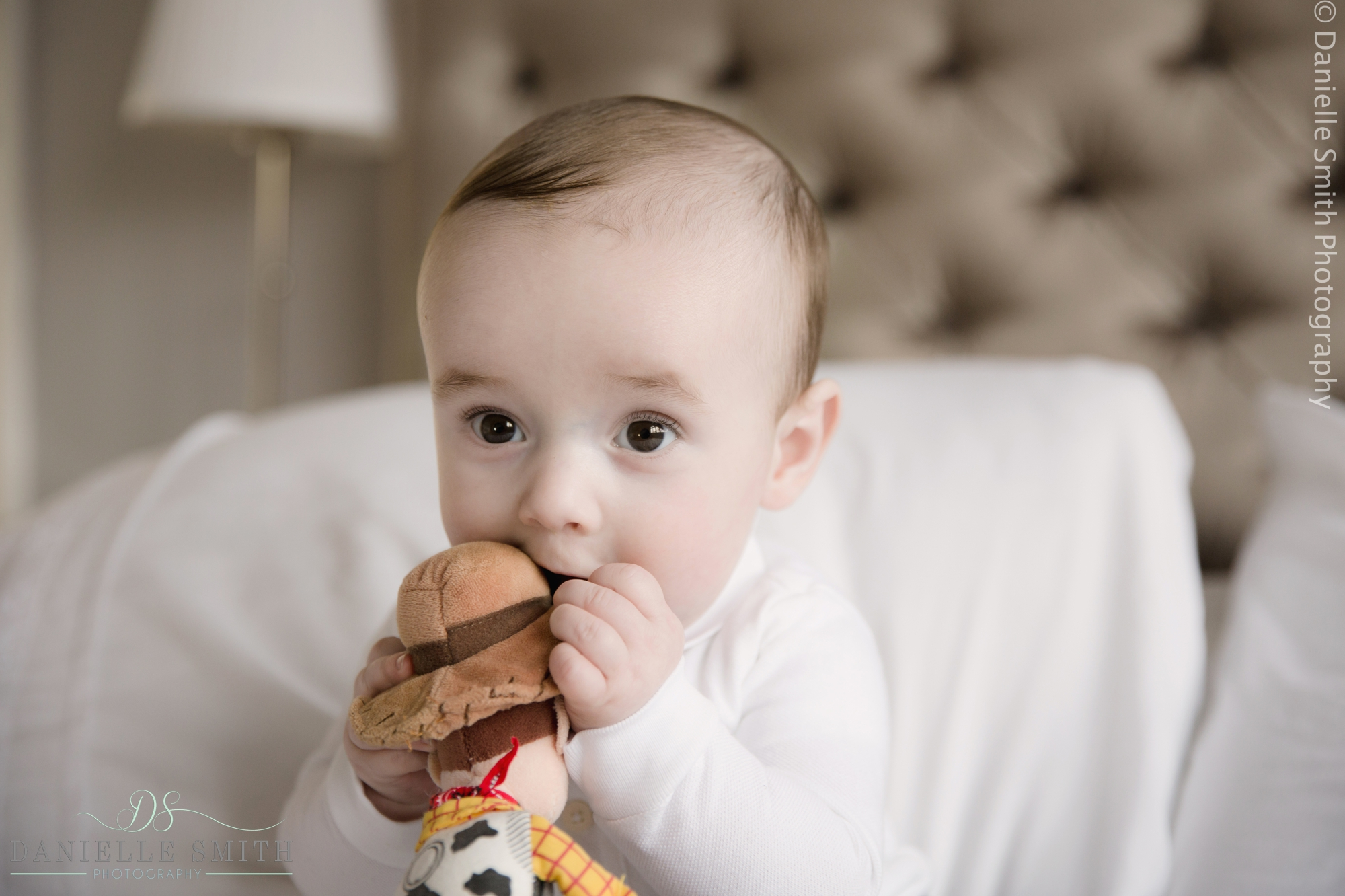 baby boy eating woody toy