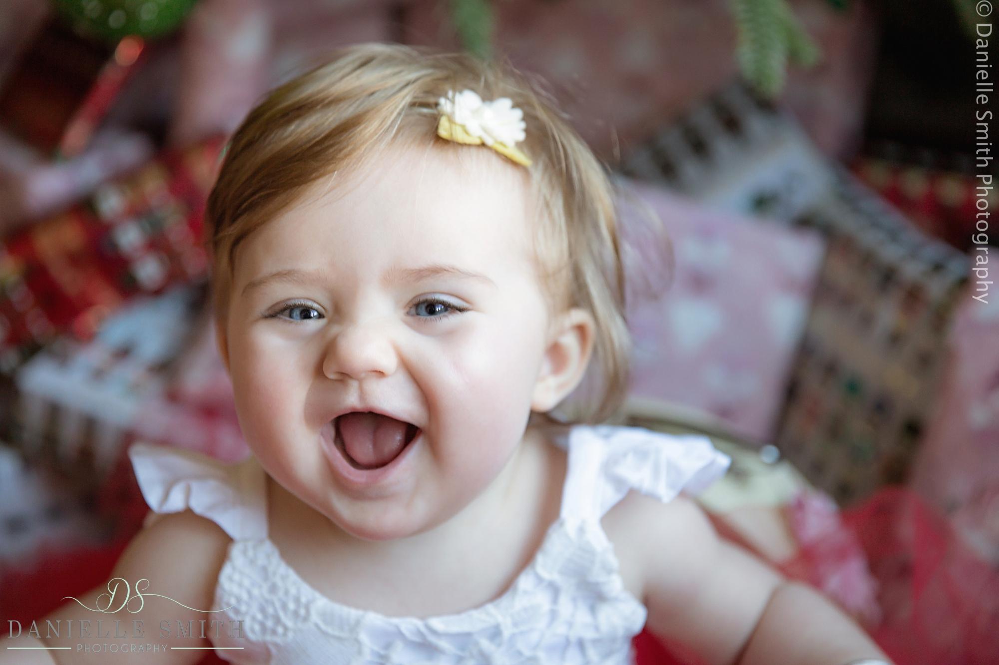 baby girl with huge smile at christmas