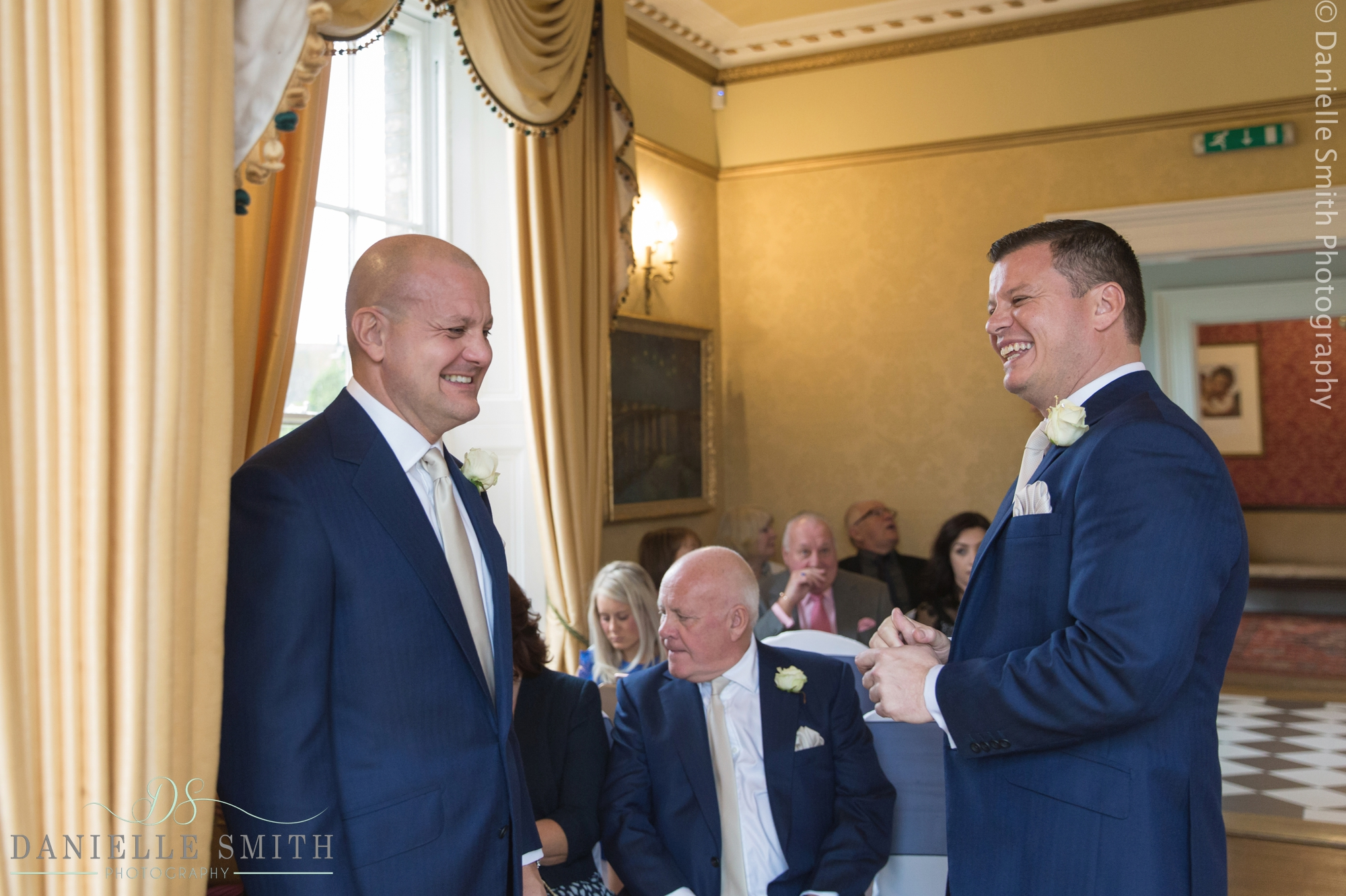 groom and best man laughing at front of ceremony - fennes intimate wedding