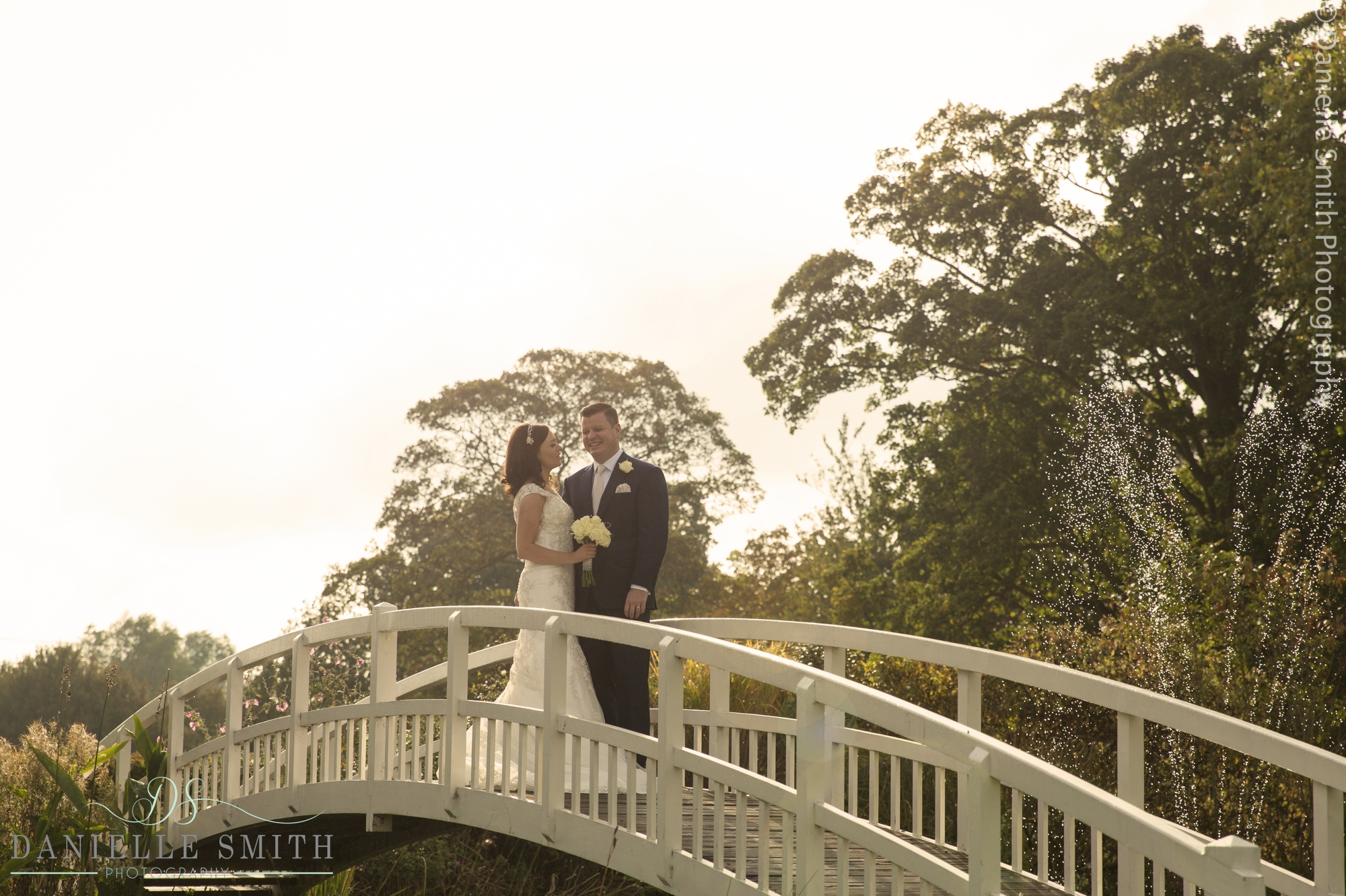 bride and groom on bridge at fennes