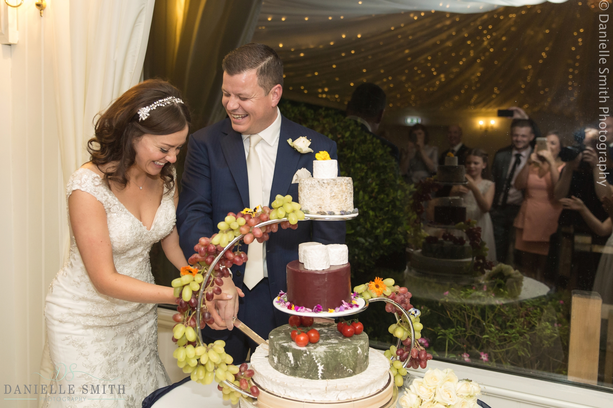 bride and groom laughing cutting cheese tower