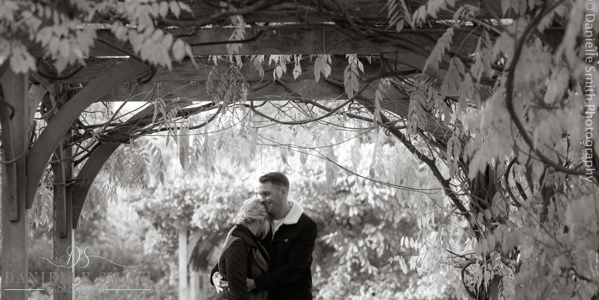 couple hugging under pergola in highlands park