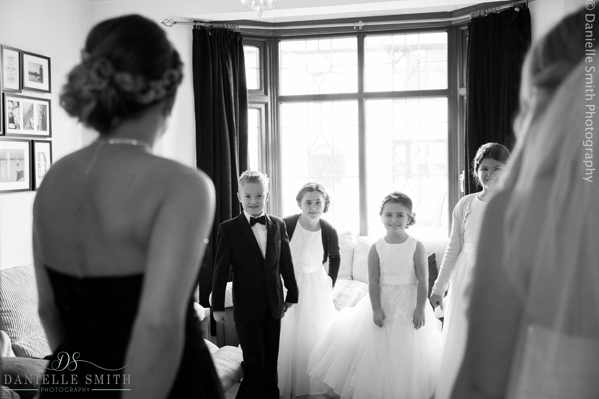 flower girls and page boy seeing bride in her dress
