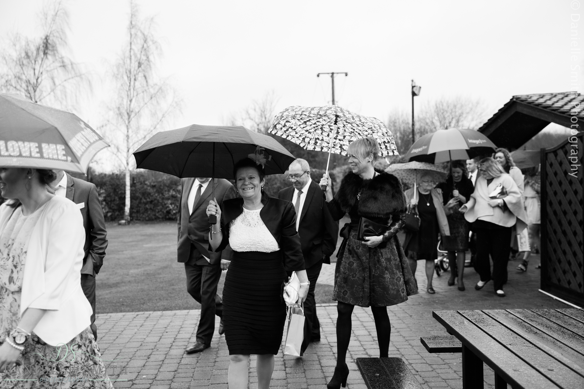 wedding guests arriving in rain with umbrellas