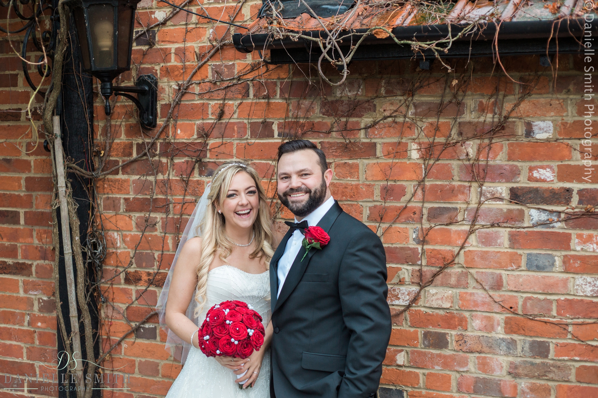 bride and groom with red rose bouquet
