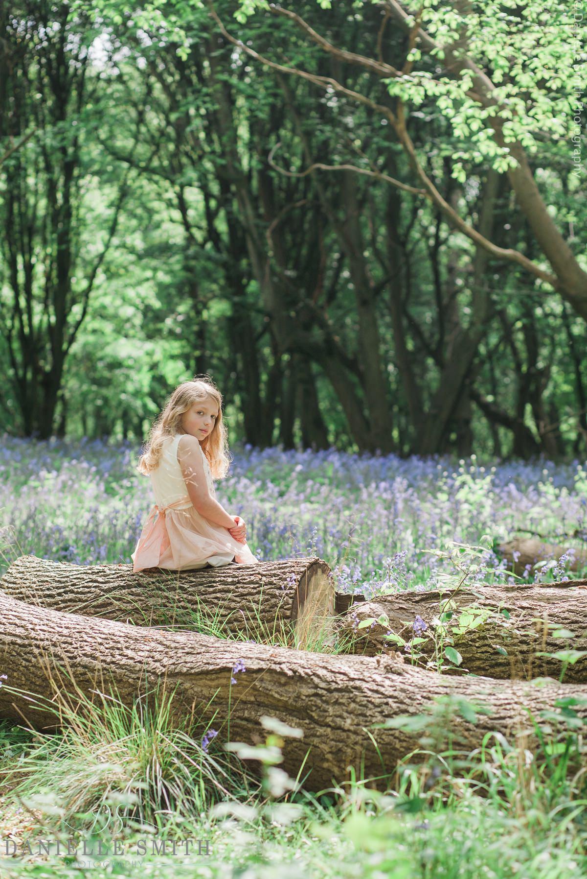 girl sitting on log in bluebell woods