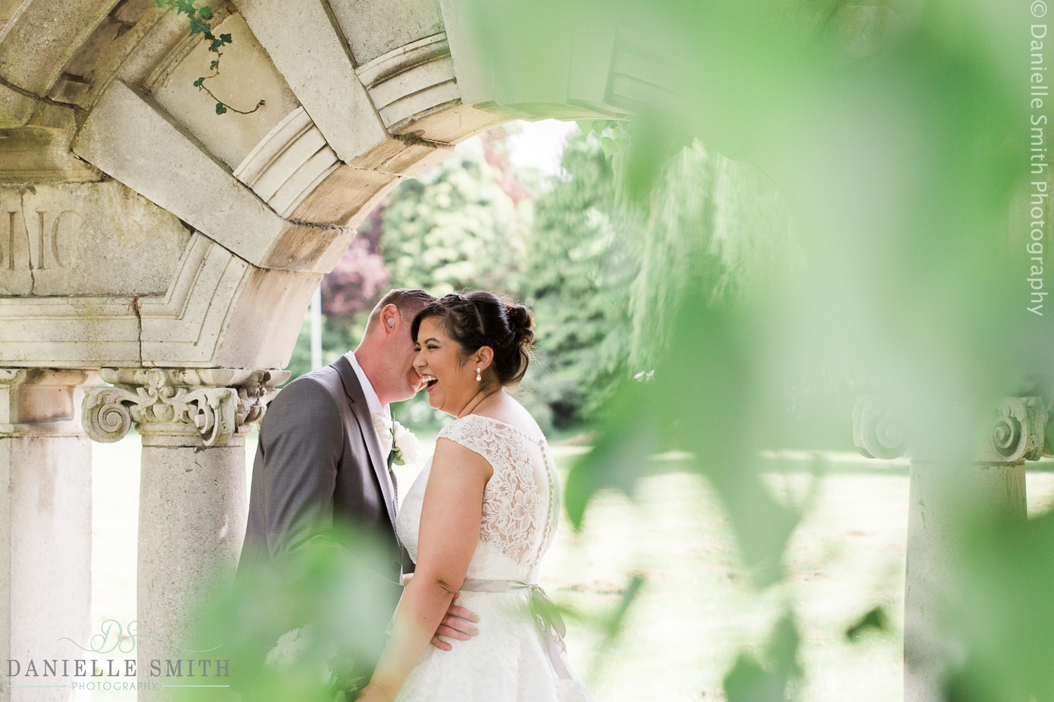 bride and groom laughing under arch - ye olde plough house wedding