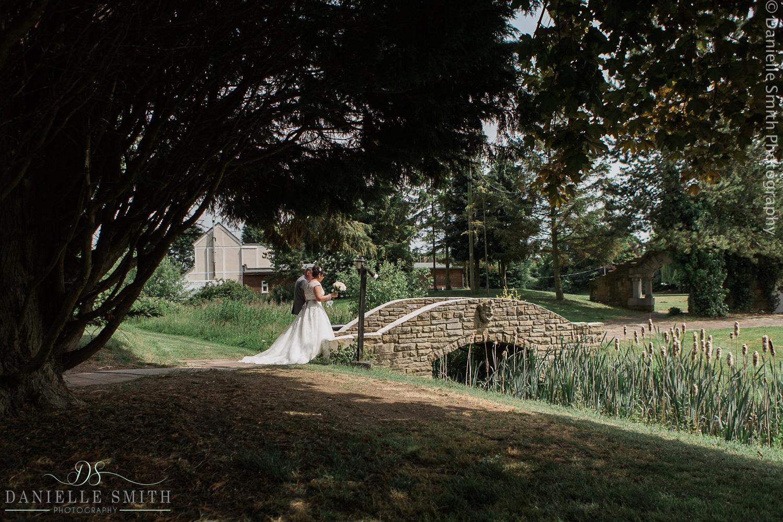 bride and groom walking over bridge