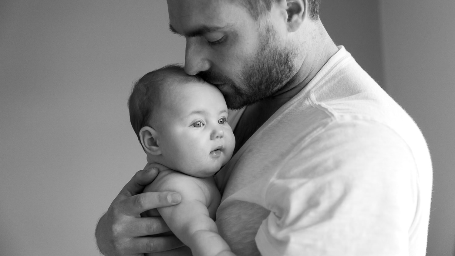 dad kissing baby girl on head