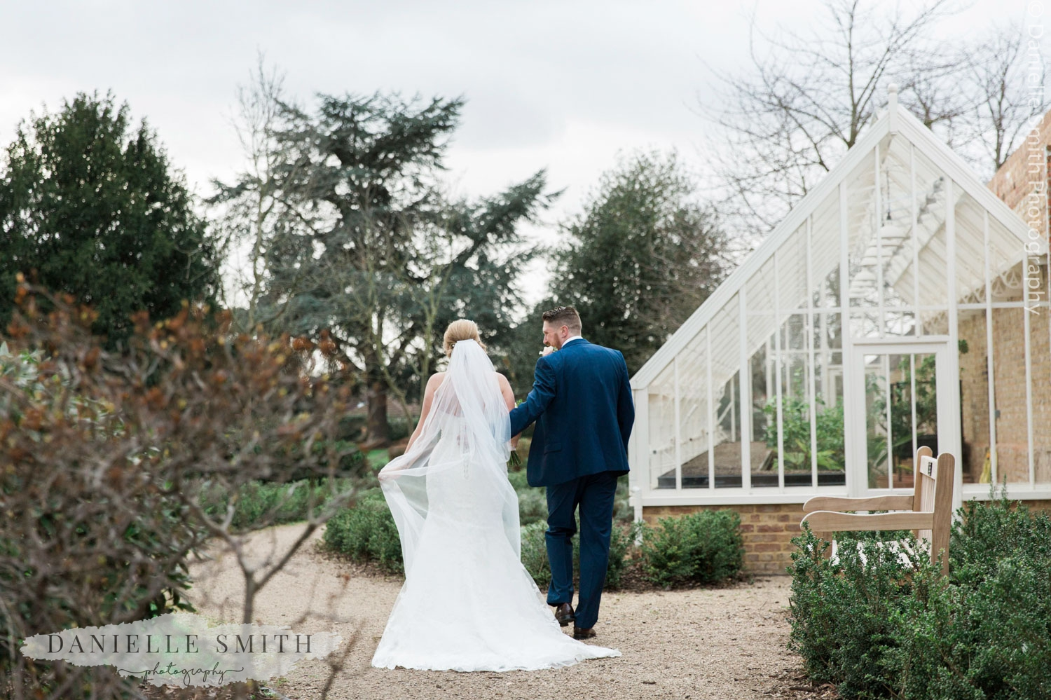 bride and groom walking through gardens at langtons