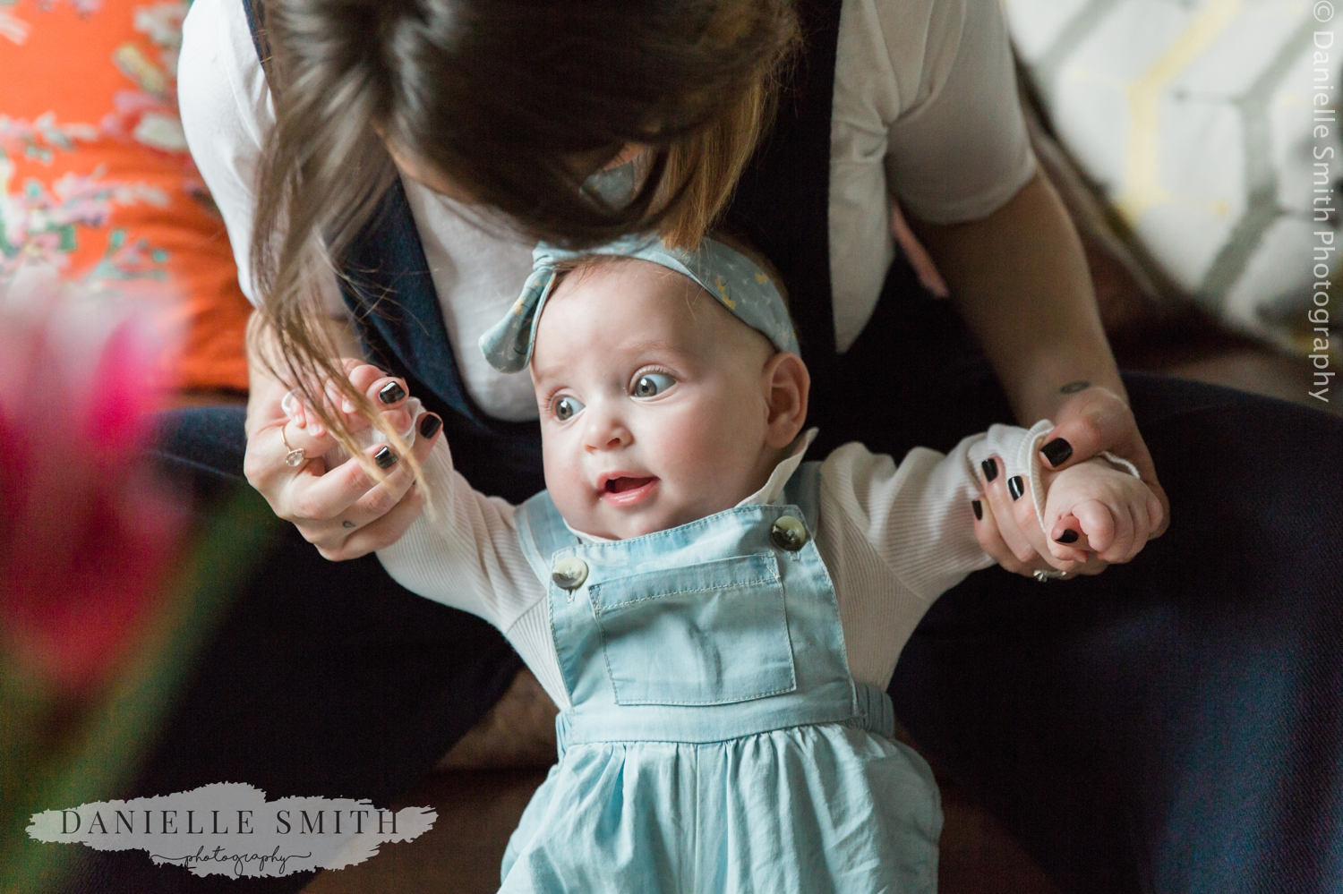 mum holding baby girl up - natural family photos