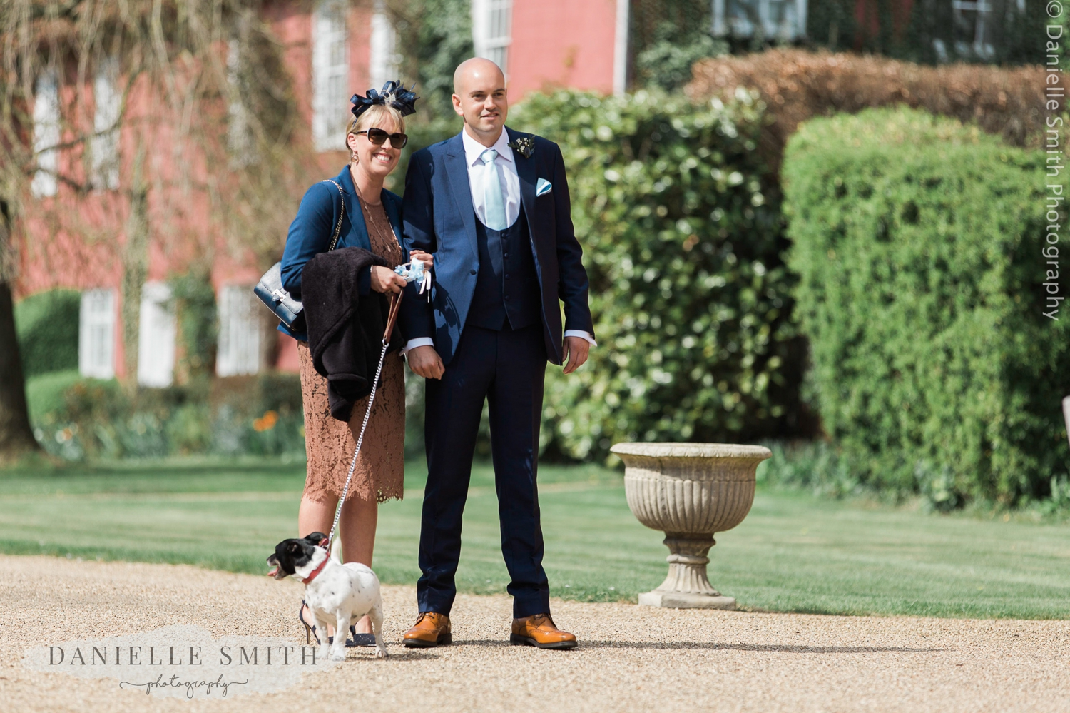 couple with dog on lead at wedding