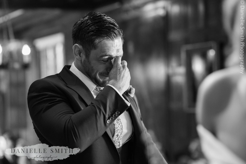 groom in tears while bride walks down the aisle