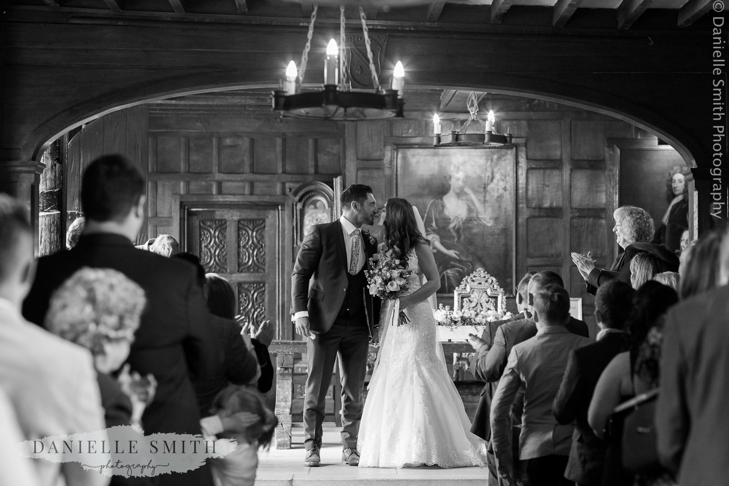 bride and groom kiss as they walk down aisle