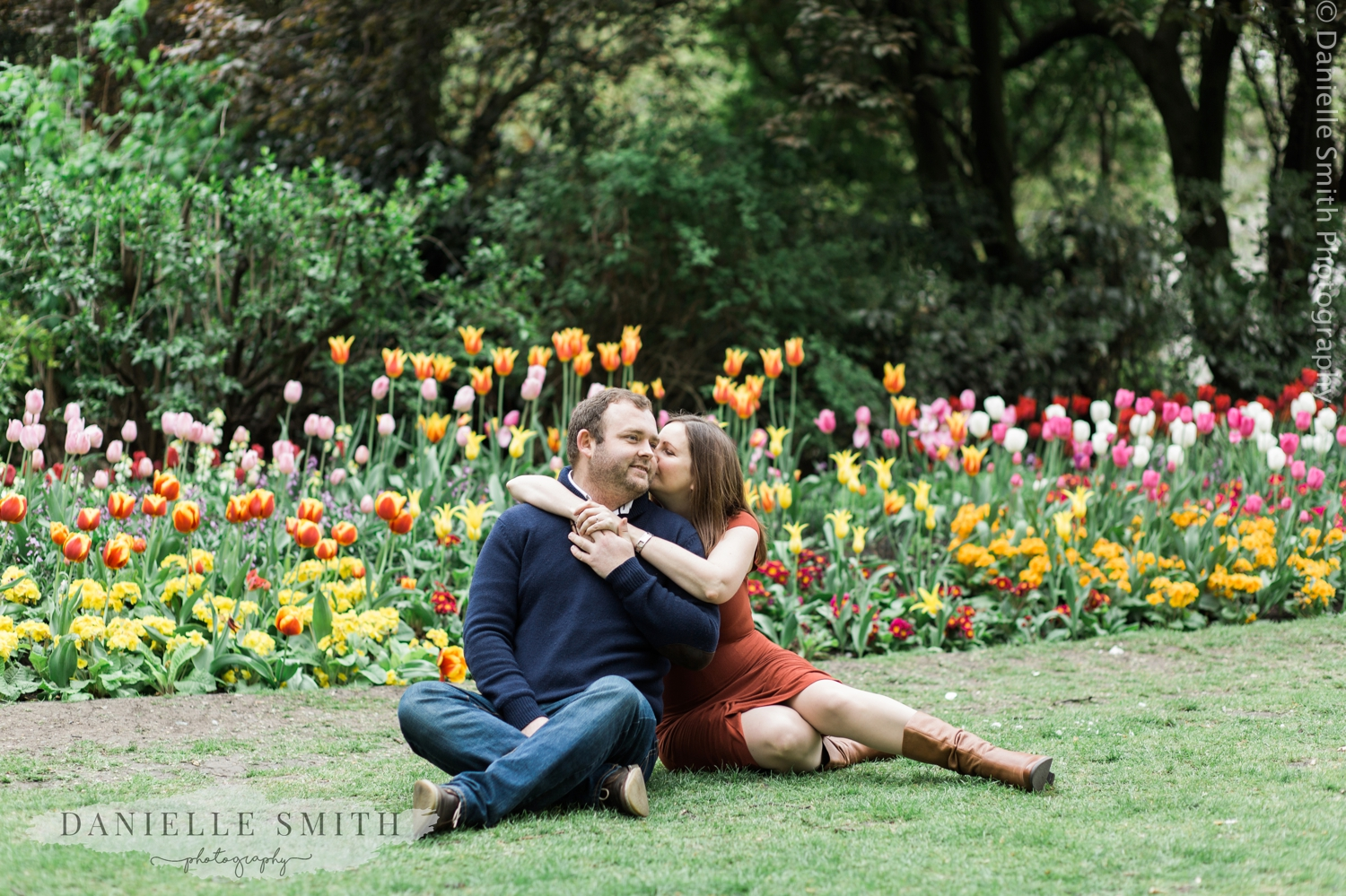 couple sitting on grass with colourful tulips