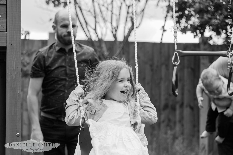 uncle pushing girl on swing