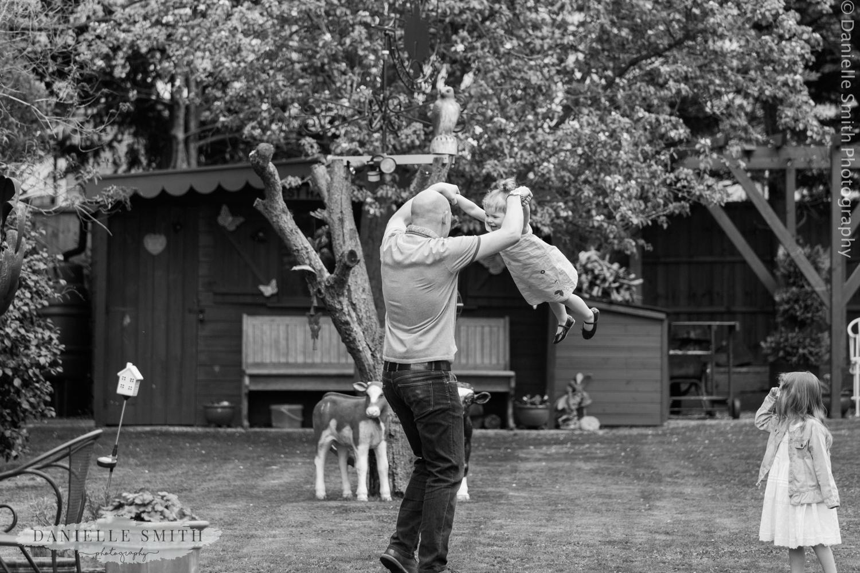 man swinging little girl round in garden