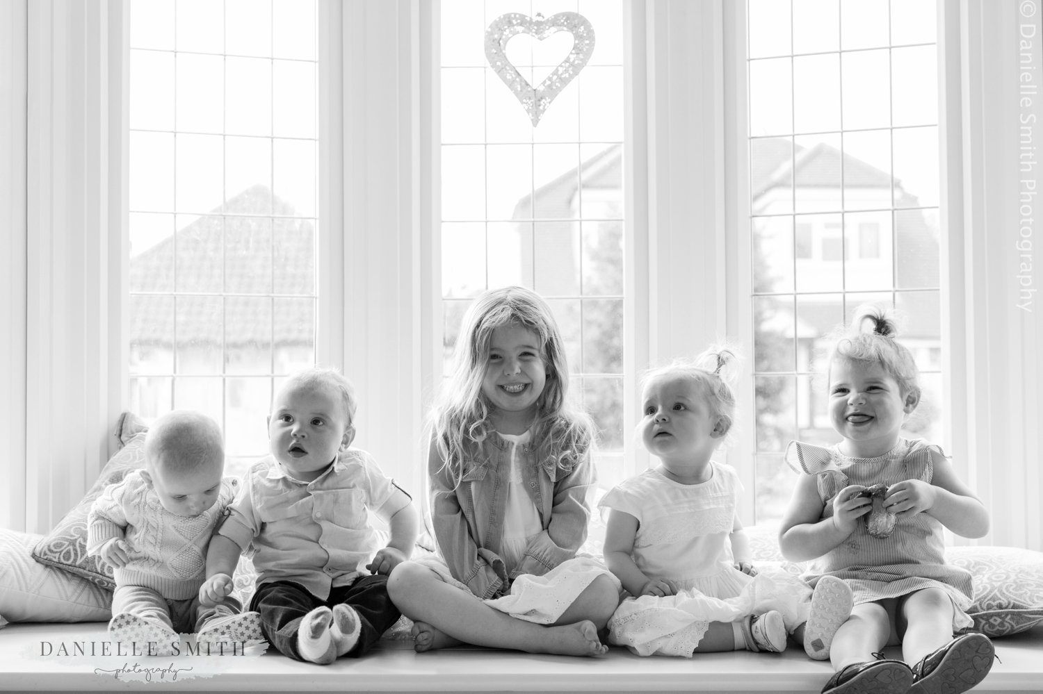 kids sitting in bay window together