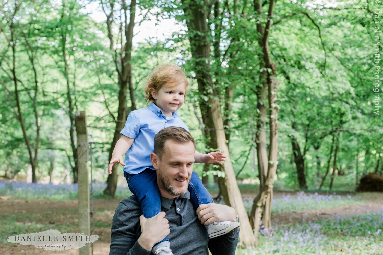 boy on dads shoulder in bluebell woods