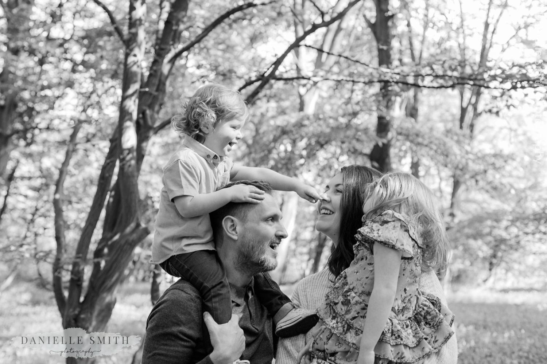 boy pressing mum nose on dads shoulders