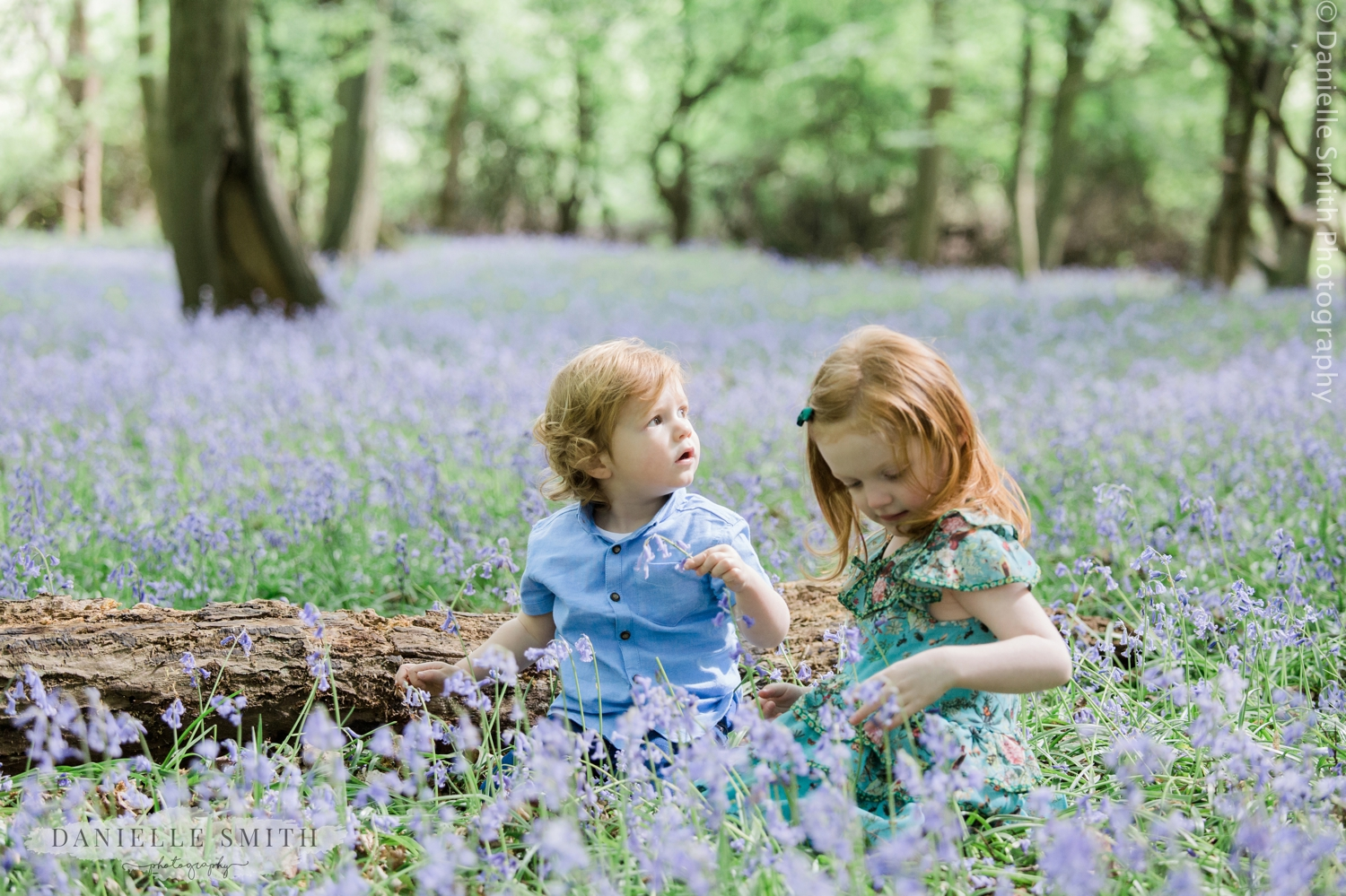brother and sister playing in bluebells
