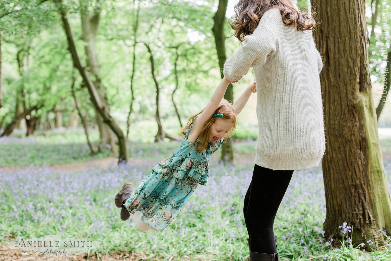 mum swinging daughter round in forest
