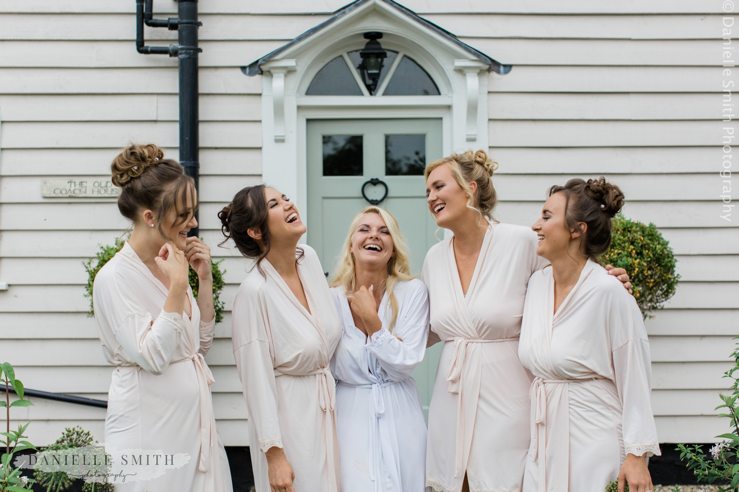 bride and bridesmaids laughing outside blake hall