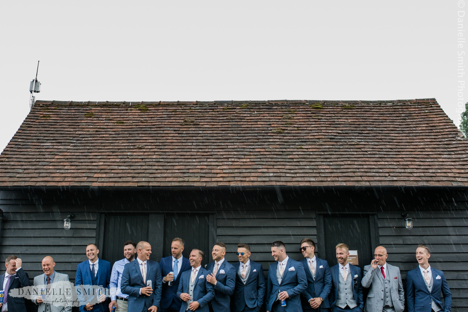 groom and groomsmen in the rain at blake hall wedding venue